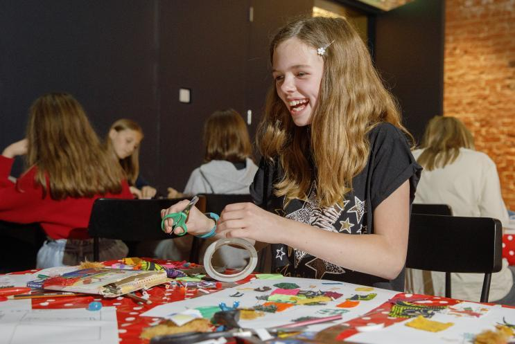 girl using tape and scissors for design