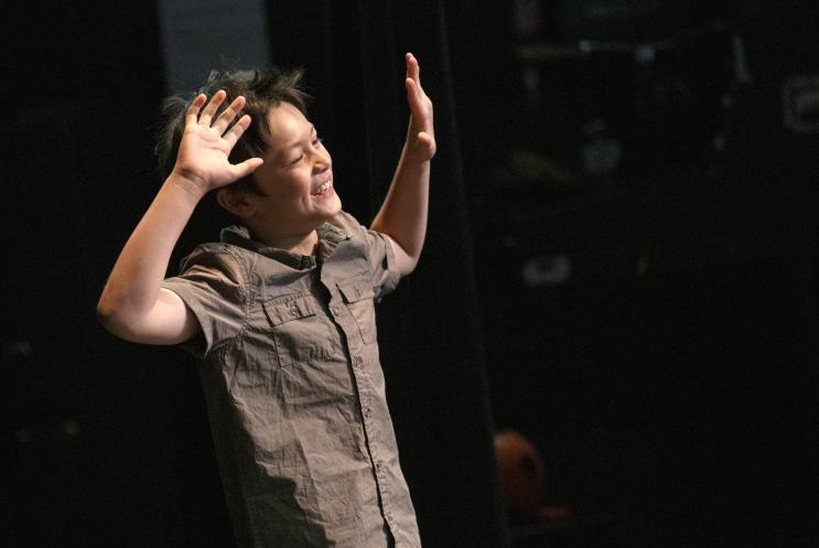 boy with hands up on stage