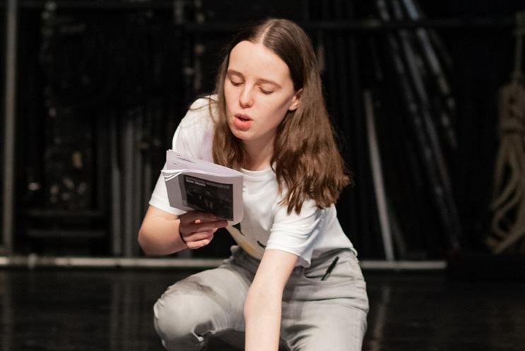 girl reading from a script on stage